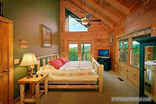 Main level bedroom with king sized bed and patio doors to deck at Flying with Eagles, a 3-bedroom cabin rental located in Pigeon Forge