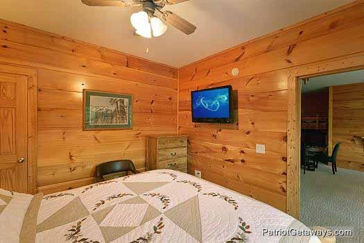 TV mounted to the wall in a first floor bedroom at Flying with Eagles, a 3-bedroom cabin rental located in Pigeon Forge