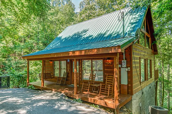 Porch swing and rockers on the covered front porch at Denim Blues, a 1-bedroom cabin rental located in Gatlinburg
