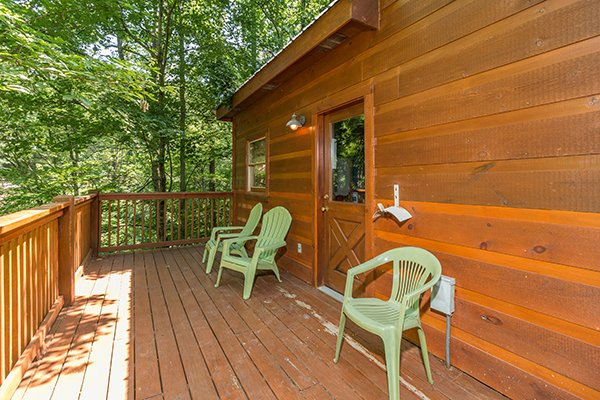 Back deck with two Adriondack chairs and a plastic chair at Denim Blues, a 1-bedroom cabin rental located in Gatlinburg