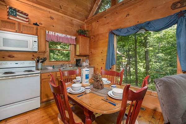 Kitchen with white appliances and dining space for four at Denim Blues, a 1-bedroom cabin rental located in Gatlinburg
