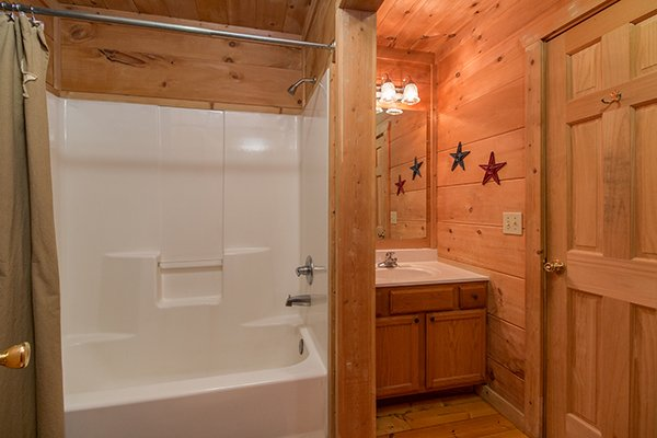 Bathroom with a tub and shower at Denim Blues, a 1-bedroom cabin rental located in Gatlinburg
