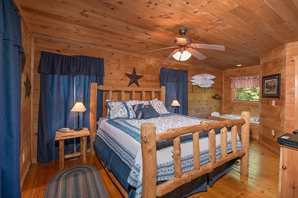 King-sized log bed in a room with two end tables and a jacuzzi at Denim Blues, a 1-bedroom cabin rental located in Gatlinburg