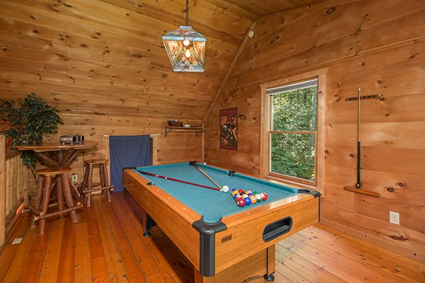 Green felted pool table in the game loft at Denim Blues, a 1-bedroom cabin rental located in Gatlinburg