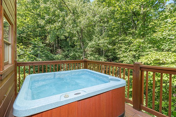 Hot tub on a deck surrounded by the woods at Denim Blues, a 1-bedroom cabin rental located in Gatlinburg