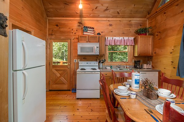 Dining space for four and a kitchen with white appliances at Denim Blues, a 1-bedroom cabin rental located in Gatlinburg