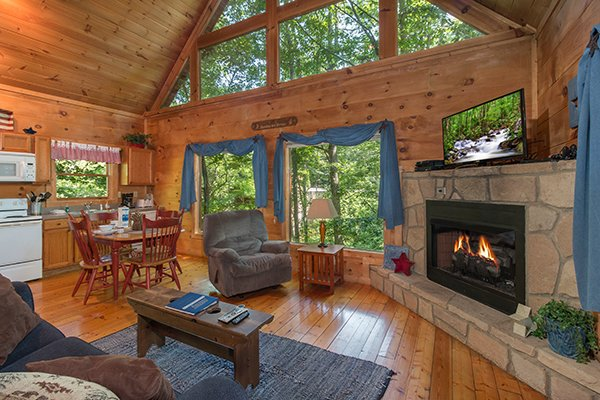 Living room, dining room, and kitchen in an open concept at Denim Blues, a 1-bedroom cabin rental located in Gatlinburg