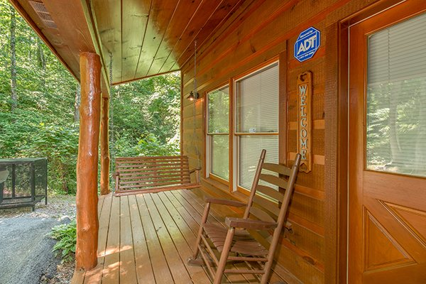 Covered front porch with a swing and rocking chairs at Denim Blues, a 1-bedroom cabin rental located in Gatlinburg