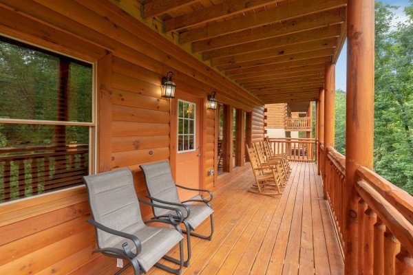 Rocking chairs and lounge chairs on a covered deck at The Pool Palace, a 5 bedroom cabin rental located in Pigeon Forge