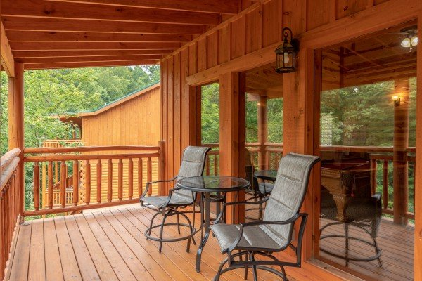 Deck seating at The Pool Palace, a 5 bedroom cabin rental located in Pigeon Forge