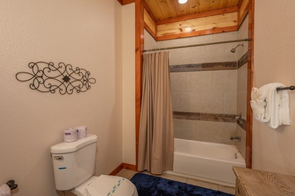 Bathroom with a tub and shower at The Pool Palace, a 5 bedroom cabin rental located in Pigeon Forge