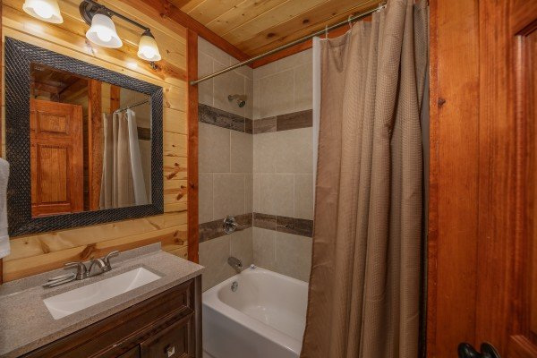 Bathroom with tub and shower at The Pool Palace, a 5 bedroom cabin rental located in Pigeon Forge