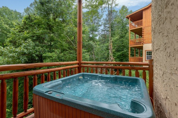 Hot tub on a covered deck at The Pool Palace, a 5 bedroom cabin rental located in Pigeon Forge
