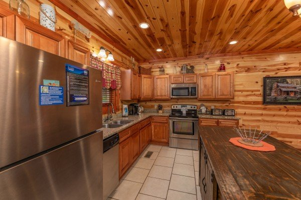 Kitchen and breakfast bar at The Pool Palace, a 5 bedroom cabin rental located in Pigeon Forge