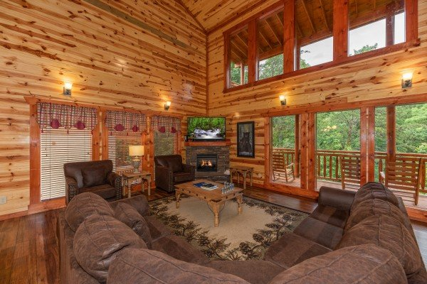 Living room with sectional sofa, fireplace, and TV at The Pool Palace, a 5 bedroom cabin rental located in Pigeon Forge