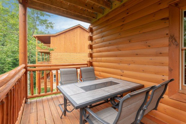 Dining space for four on the covered deck at The Pool Palace, a 5 bedroom cabin rental located in Pigeon Forge