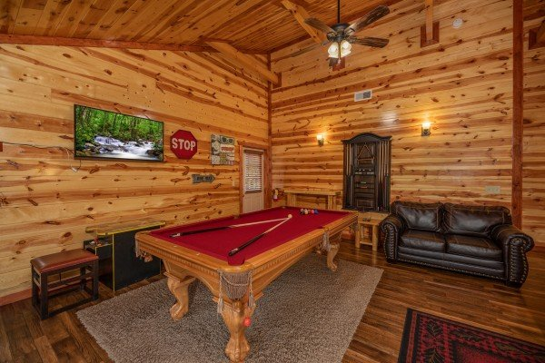 Pool table and TV at The Pool Palace, a 5 bedroom cabin rental located in Pigeon Forge