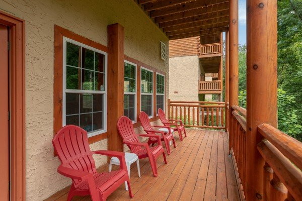 Red Adirondack chairs on the lower deck at The Pool Palace, a 5 bedroom cabin rental located in Pigeon Forge