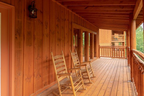 Rocking chairs on a covered deck at The Pool Palace, a 5 bedroom cabin rental located in Pigeon Forge