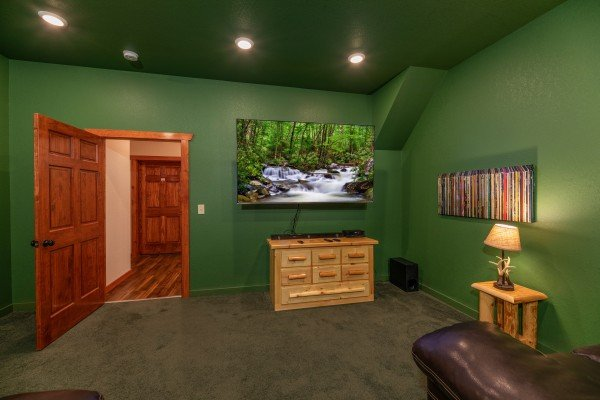 Big screen TV and console in the theater room at The Pool Palace, a 5 bedroom cabin rental located in Pigeon Forge