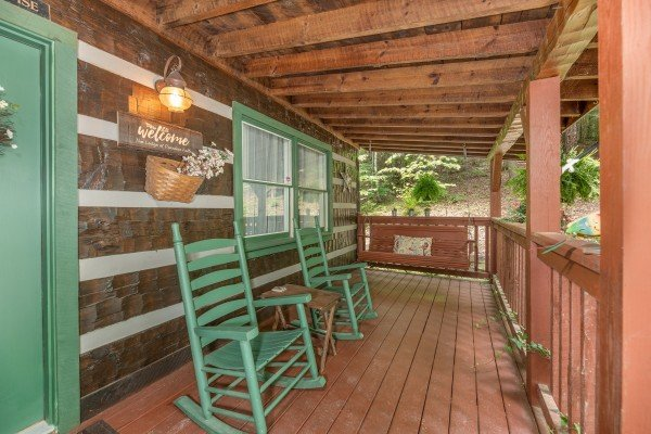 Front porch with rocking chair and swing at The Lodge at Paradise Falls, a 4 bedroom cabin rental located in Pigeon Forge