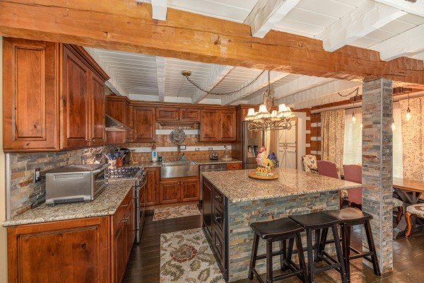 Kitchen with breakfast bar and stainless appliances at The Lodge at Paradise Falls, a 4 bedroom cabin rental located in Pigeon Forge