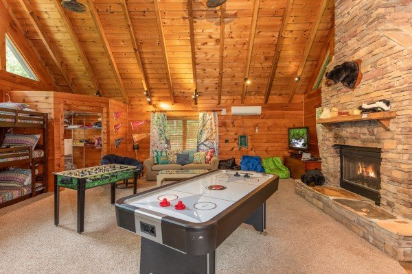 Air hockey, foosball, and a fireplace in the kids game area at The Lodge at Paradise Falls, a 4 bedroom cabin rental located in Pigeon Forge