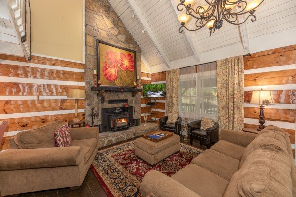 Living room with vaulted ceiling, fireplace, and TV at The Lodge at Paradise Falls, a 4 bedroom cabin rental located in Pigeon Forge