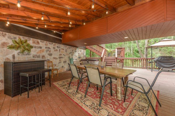 Dining table, outdoor bar, and grill at The Lodge at Paradise Falls, a 4 bedroom cabin rental located in Pigeon Forge