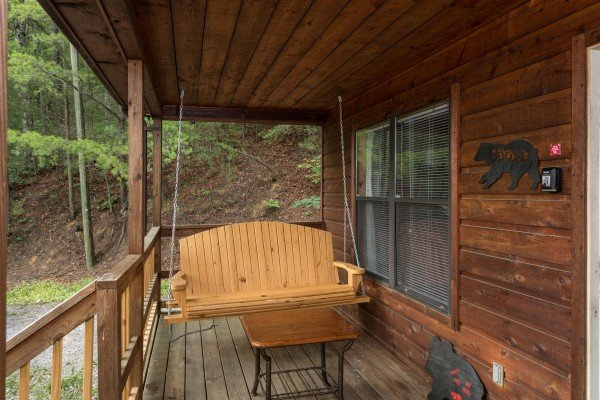 Swing on the covered porch at Peace & Quiet, a 3 bedroom cabin rental located in Pigeon Forge