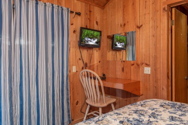 Mirror, desk, and TV in the bedroom at Peace & Quiet, a 3 bedroom cabin rental located in Pigeon Forge