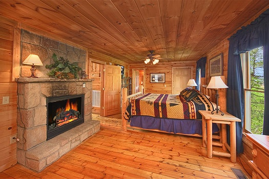 bedroom with king bed and fireplace at trapper's trace a 2 bedroom cabin rental located in gatlinburg