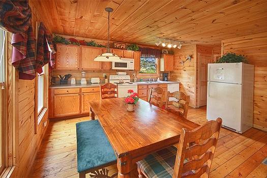 Kitchen with white appliances and dining space for six at Trapper's Trace, a 2 bedroom cabin rental located in Gatlinburg