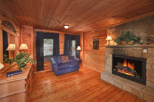 master bedroom fireplace and seating area at trapper's trace a 2 bedroom cabin rental located in gatlinburg