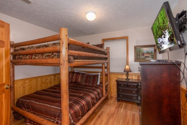 Room with twin bunk bed, dresser, and television at Burrow Inn, a 4-bedroom cabin rental located in Pigeon Forge
