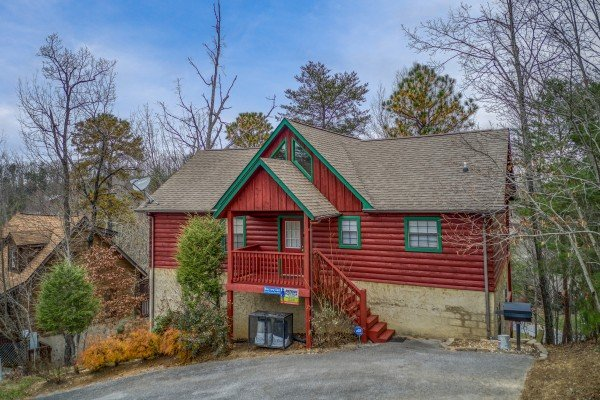 Front exterior of cabin with a grill and parking at Burrow Inn, a 4-bedroom cabin rental located in Pigeon Forge