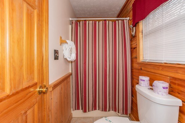 Bathroom with a tub and shower at Burrow Inn, a 4-bedroom cabin rental located in Pigeon Forge
