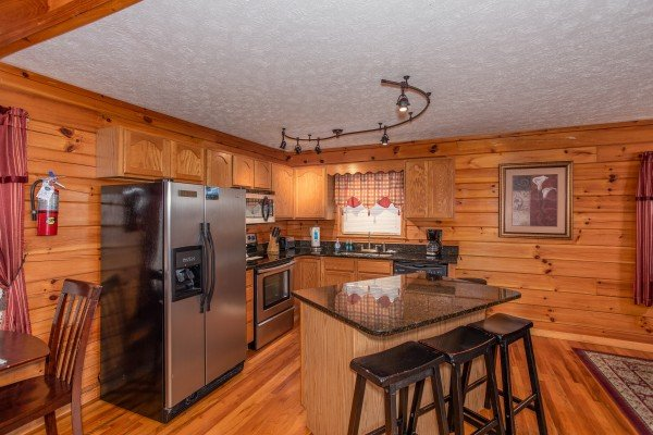 Kitchen with stainless steel appliances and counter seating for three at Burrow Inn, a 4-bedroom cabin rental located in Pigeon Forge
