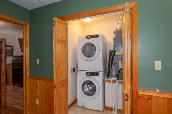 Stacked washer and dryer in a laundry room at Burrow Inn, a 4-bedroom cabin rental located in Pigeon Forge