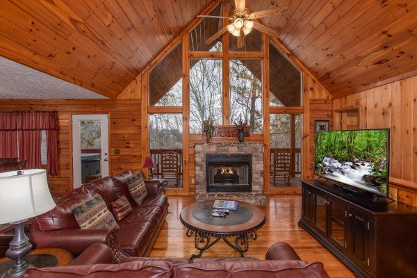 Vaulted living room with floor-to-ceiling windows, a large TV, and a fireplace at Burrow Inn, a 4-bedroom cabin rental located in Pigeon Forge