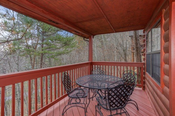 Outdoor dining space for four on a covered deck at Burrow Inn, a 4-bedroom cabin rental located in Pigeon Forge