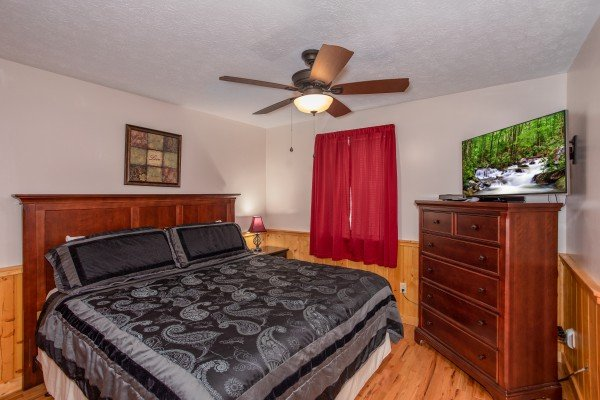 Bedroom with a king-sized bed, dresser, and television at Burrow Inn, a 4-bedroom cabin rental located in Pigeon Forge
