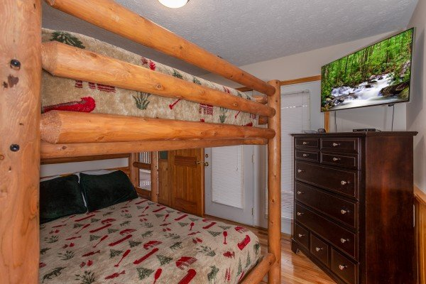 Bunk room with a dresser, television, and deck access at Burrow Inn, a 4-bedroom cabin rental located in Pigeon Forge