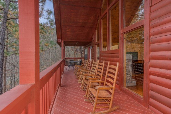 Six rocking chairs lined up on a covered deck at Burrow Inn, a 4-bedroom cabin rental located in Pigeon Forge