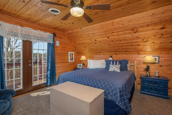 Bedroom with king bed, night stands, lamps, and deck access at Leconte Nirvana, a 3 bedroom cabin rental located in Pigeon Forge
