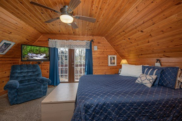 Chair, TV, and deck access in a bedroom at Leconte Nirvana, a 3 bedroom cabin rental located in Pigeon Forge