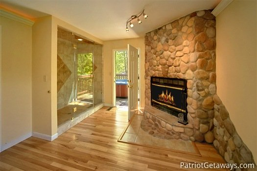 Stone fireplace next to in room shower at Quality Time, a 1 bedroom cabin rental located in Gatlinburg