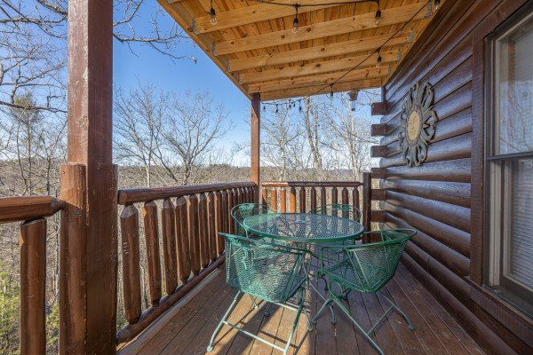 Dining table for four on a covered deck at Nascar Nation, a 2 bedroom cabin rental located in Pigeon Forge