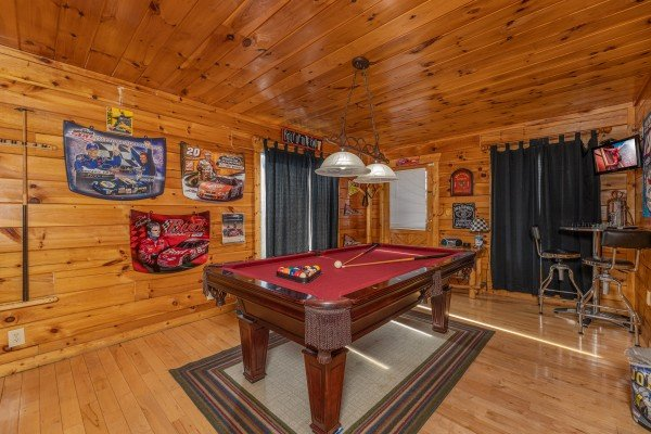 Red felt pool table in a game room at Nascar Nation, a 2 bedroom cabin rental located in Pigeon Forge