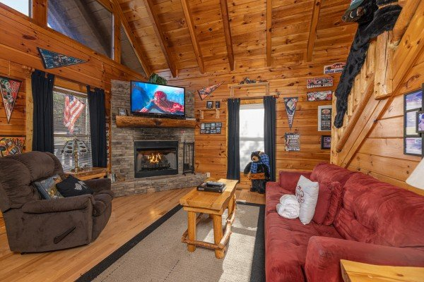 Living room with fireplace and TV at Nascar Nation, a 2 bedroom cabin rental located in Pigeon Forge